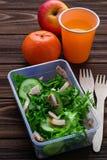 Scatola di pranzo con insalata, la mela, il mandarino ed il succo Immagini Stock