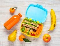 Scatola di pranzo con le bevande, i panini ed i frutti Fotografia Stock