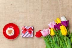 Scatola di regalo ed il cappuccino vicino ai fiori Immagini Stock Libere da Diritti