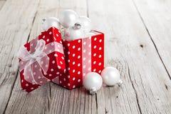 Scatola di regalo rossa di Natale in pieno di bagattella di bianco di natale Fotografia Stock