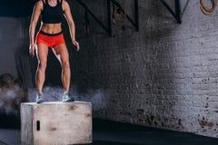 Scatola di salto della donna Donna di forma fisica che fa allenamento di salto della scatola alla palestra adatta dell'incrocio Fotografia Stock