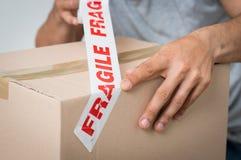 Scatola di sigillamento dell'uomo con adesivo fragile immagini stock