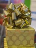 Scatola dorata del regalo di compleanno o di Natale con la fine del nastro dell'oro su Fotografia Stock Libera da Diritti