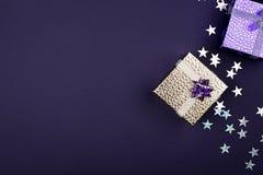 Scatola dorata festiva su un fondo porpora con le stelle delle scintille Fondo festivo per il vostro progetto orizzontale deep immagine stock