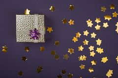 Scatola dorata festiva su un fondo porpora con le stelle delle scintille Fondo festivo per il vostro progetto orizzontale deep immagini stock