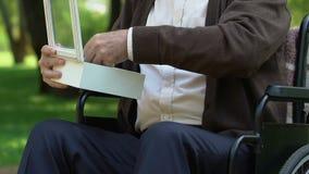 Scatola handicappata di apertura dell'uomo anziano con la medaglia della guerra, memorie stressanti della gioventù video d archivio