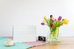Scatola leggera con lo spazio della copia e fiori sullo scrittorio di legno con bianco Fotografia Stock