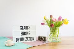 Scatola leggera con scrittura di ottimizzazione del motore di ricerca sullo scrittorio di legno Fotografia Stock