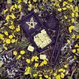 Scatola nera con le rune e le candele di legno in fiori immagine stock