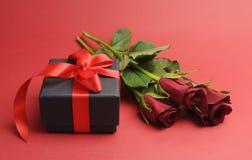 Scatola nera di giorno di biglietti di S. Valentino con il regalo e la rosa rossa rossi del nastro Immagine Stock