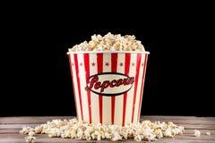 Scatola piena con popcorn e rovesciata sul retro scrittorio di legno immagine stock libera da diritti
