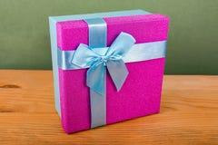 scatola porpora per i regali su un fondo verde, regali di Natale, nastro blu, arco blu di Natale Immagine Stock