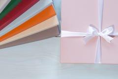 Scatola rosa con l'arco bianco, su fondo di legno, scatole di cartone variopinte immagine stock