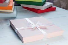 Scatola rosa con l'arco bianco, su fondo di legno, scatole di cartone variopinte immagine stock libera da diritti
