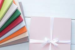 Scatola rosa con l'arco bianco, su fondo di legno, scatole di cartone variopinte fotografia stock libera da diritti