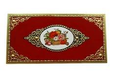 Scatola rossa d'annata con i fiori e gli ornamenti dorati, isolati su fondo bianco Fotografia Stock