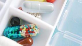 Scatola settimanale della pillola con le pillole mediche su fondo blu video d archivio