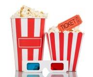 Scatola a strisce piena con popcorn, il biglietto di film ed i vetri 3D isolati su un bianco Immagini Stock