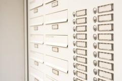 Scatole bianche della posta per le lettere ed anelli della campana alla casa fotografie stock