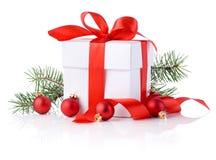 Scatole bianche, nastro rosso, ramo di albero e palla di natale  Immagine Stock