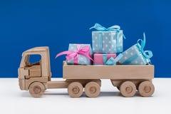 Scatole con i regali in blu con i pois bianchi e la carta rosa, camion di legno del giocattolo fortunato Concetto di festa immagini stock libere da diritti