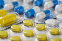 Scatole con le pillole mediche gialle e le pillole bianche blu Immagini Stock Libere da Diritti