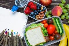 Scatole della refezione con il panino, la frutta, le verdure e la bottiglia di acqua con le matite colorate ed il quaderno vuoto Immagini Stock