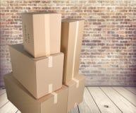 Scatole di cartone differenti nella sala sul pavimento di legno Fotografia Stock