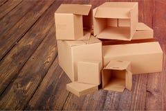 Scatole di cartone differenti su fondo di legno Immagine Stock