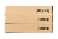 Scatole di cartone isolate su un fondo bianco con il codice a barre del campione Fotografie Stock