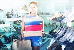 Scatole femminili della tenuta dell'adolescente della testarossa nel boutique delle scarpe Immagini Stock