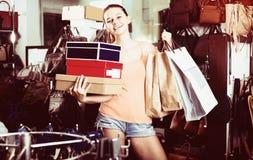 Scatole femminili sorridenti della tenuta dell'adolescente nel boutique delle scarpe Fotografie Stock