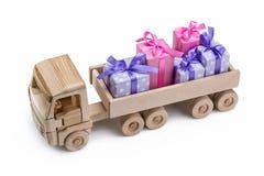 Scatole nella festa che imballa dietro al camion di legno del giocattolo Concetto di festa immagine stock libera da diritti