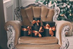 Scatole nere avvolte del regalo con i nastri come regali di Natale su una sedia Fotografia Stock Libera da Diritti