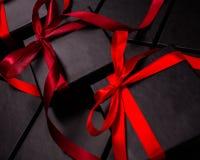 Scatole nere per i regali d'imballaggio con gli archi rossi Immagine Stock Libera da Diritti