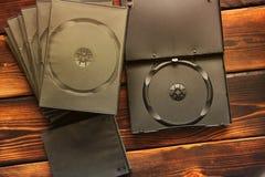 Scatole per le unità CD su un fondo di legno fotografie stock libere da diritti