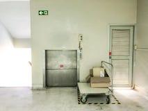 Scatole sul carrello davanti al mini elevatore per la cosa di movimento su e giù Fotografia Stock