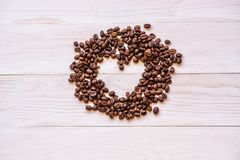 Scatter сердца кофейных зерен на белой деревенской предпосылке Взгляд сверху стоковое фото
