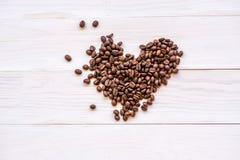 Scatter сердца кофейных зерен на белой деревенской предпосылке Взгляд сверху стоковые изображения