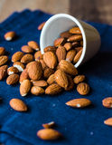 Scatter nuts almonds in a white bowl on blue napkin Stock Images