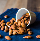Scatter nuts almonds in a white bowl on blue napkin Royalty Free Stock Image