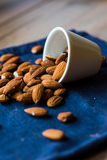 Scatter nuts almonds in a white bowl on blue napkin Stock Photos
