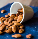 Scatter nuts almonds in a white bowl on blue napkin Stock Image