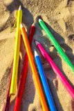 Scattered on the beach in the sand colored wooden pencils for dr. Awing, sunlight Royalty Free Stock Image