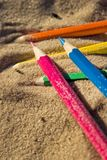 Scattered on the beach in the sand colored wooden pencils for dr. Awing, sunlight Stock Images