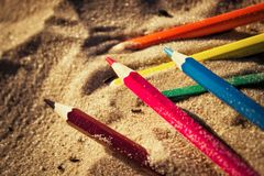 Scattered on the beach in the sand colored wooden pencils for dr. Awing, sunlight Stock Photos