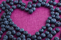 Scattered blueberries heart shaped. Scattered blueberries formed heart shape on a pink jute tablecloth close up stock images
