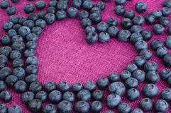 Scattered blueberries heart shaped. Scattered blueberries formed heart shape on a pink jute tablecloth close up royalty free stock photography