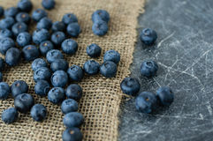 Scattered blueberries. On jute tablecloth and chalkboard background close up stock photo