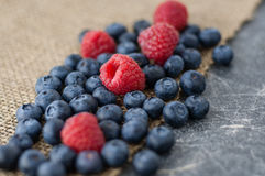 Scattered blueberries and raspberries. On jute tablecloth and chalkboard background close up, diagonal royalty free stock photography